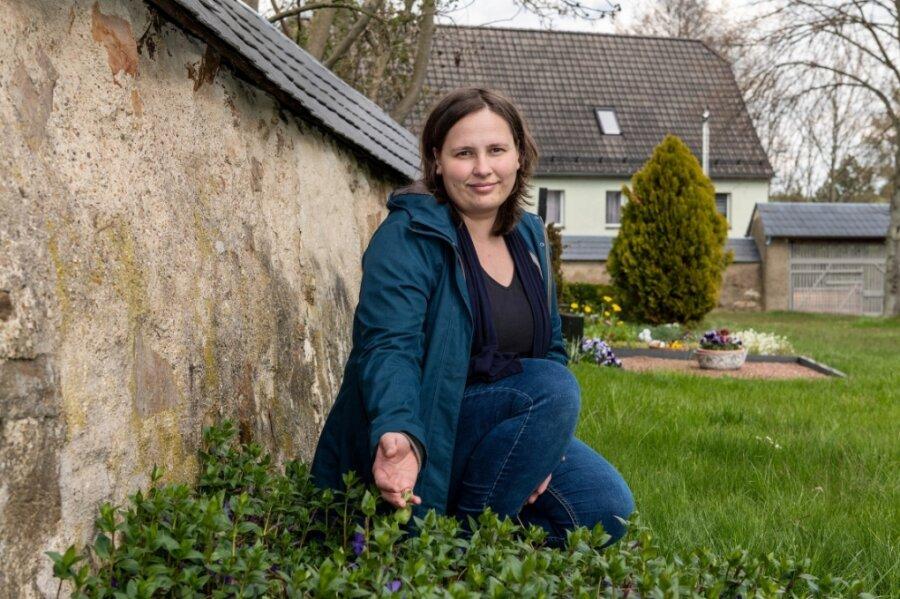 Andrea Schnabel vom Kirchenvorstand in Topfseifersdorf zeigt auf dem Friedhof an der Kirche, wo die Grabanlage für Sternenkinder entstehen soll. Zur Umsetzung hofft die Kirchgemeinde Seelitzer Land auf Spenden.