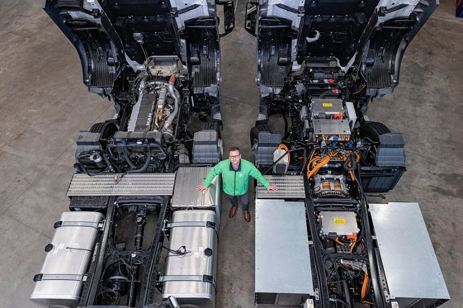 Vom Verbrenner (l.) zum Stromer (r.): Framo-Mitarbeiter Michael Klopfer zwischen zwei Lkw. Der Dieselmotor der links geparkten MAN-Zugmaschine wird noch durch ein Elektroaggregat getauscht.