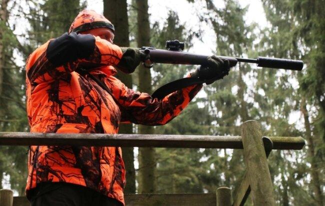 Jagdleiter Udo Lüttschwager mit Sicherheitskleidung auf dem Jagdstand und Jagdwaffe im Anschlag