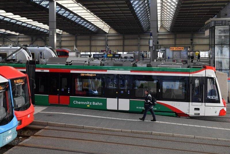 Ein Straßenbahnzug (r) vom Chemnitzer Modell fährt aus dem Hauptbahnhof.