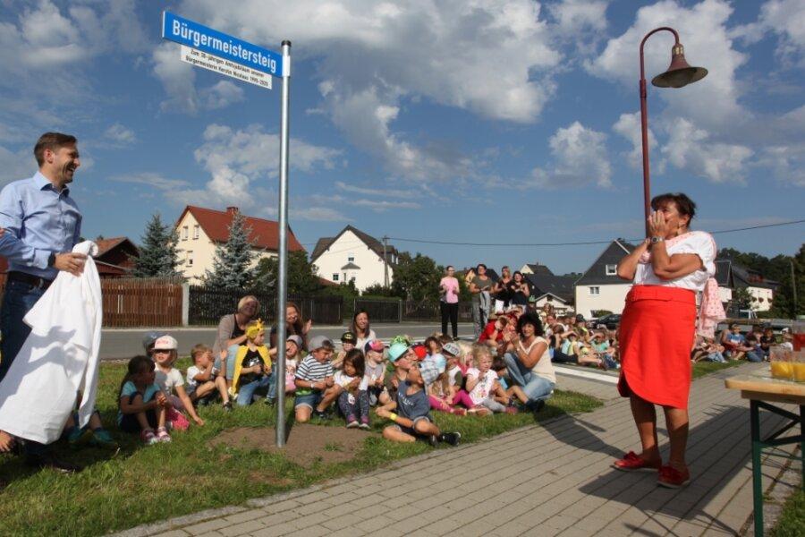 """In Hartmannsdorf gibt es seit Freitag einen """"Bürgermeistersteig"""" zu Ehren von Bürgermeisterin Kerstin Nicolaus (CDU). Christfried Nicolaus, Anwärter für das Amt, enthüllte das Schild, das das Wirken seiner Mutter über drei Jahrzehnte für ihr Dorf würdigen soll."""