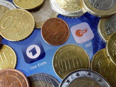 Euromünzen liegen neben den Logos der Apps von ARD und ZDF.