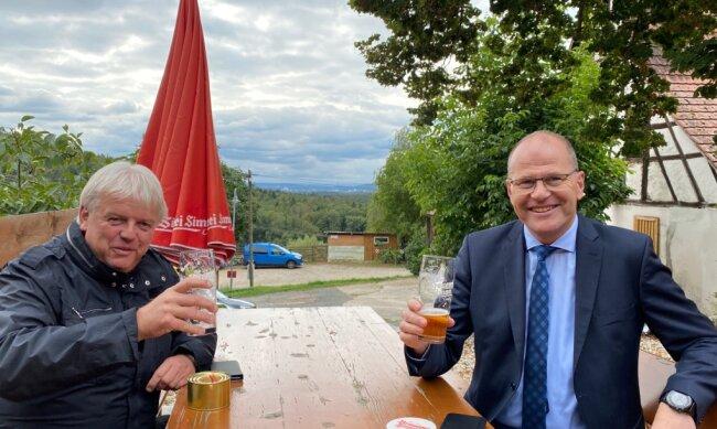 Ein Prosit auf die Einheit: Die beiden Bürgermeister Dieter Greysinger (l.) und Jens Fankhänel haben schon ein Bier auf den Tag der Deutschen Einheit getrunken. Sie leiten heute als Zugezogene jeweils die Geschicke in der Kommune, die genau in der Heimatregion des anderen liegt.