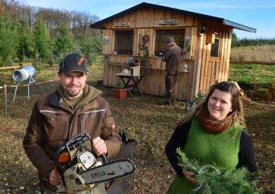 Matthias Schöne zückt schon mal die Kettensäge für ein Foto, bald kürzt er damit für seine Kunden die Baumstämme. Lebensgefährtin Mandy Lehmann hilft ihm auf der Weihnachtsbaumplantage in Mittweida.