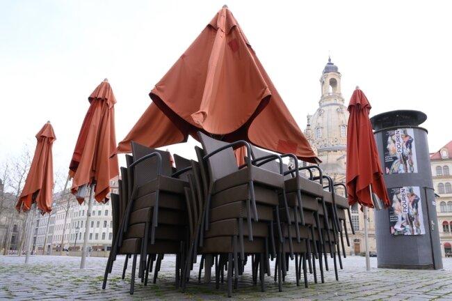 Stühle vor einem geschlossenen Restaurant auf dem Neumarkt vor der Frauenkirche. Wegen der hohen Zahl der Corona-Infektionen werden in Dresden Lockerungen wieder rückgängig gemacht.