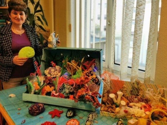 Olga Bartle vor den beiden gehäkelten Korallenriffen.