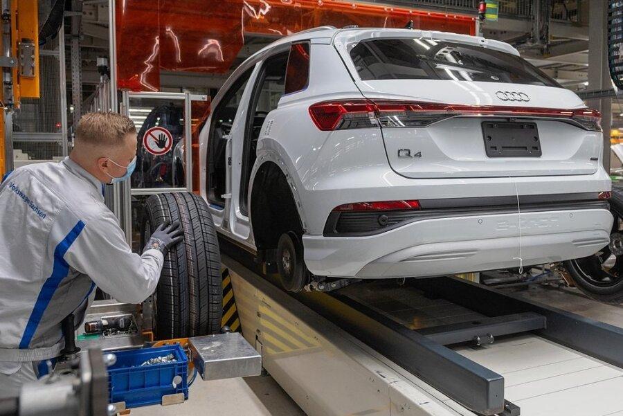 Mitarbeiter im Volkswagen-Werk in Zwickau montieren einen Audi Q4 e-tron. Ein gutes halbes Jahr nach dem Start des SUV hat sich Zwickau für Audi zum größten Produktionsstandort für E-Autos entwickelt.