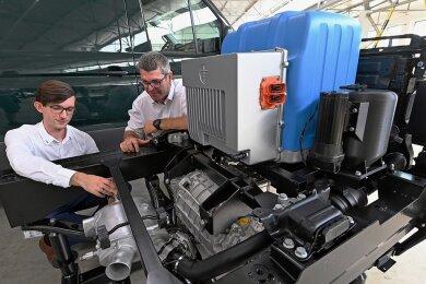Ben Wendrock (links) und Jens Ruffert von der Fahrzeug-Entwicklung Sachsen (FES) zeigen den Prototypen eines Wasserstoffantriebs für Nutzfahrzeuge.