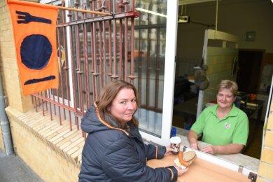Einen zusätzlichen Verkauf bietet der Imbiss im Sozialen Werk Das Netz in Oelsnitz an. Silke Dunger (rechts) nutzt das Fenster zur Straße - hier mit Mitarbeiterin Yvonne Rahm, für das Foto ohne Mundschutz.