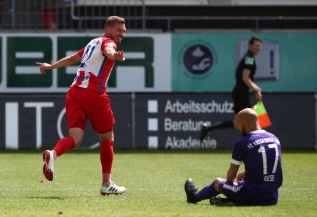 Heidenheims Konstantin Kerschbaumer bejubelt sein Tor zum 2:0. Aues Aues Philipp Riese sitzt am Boden.