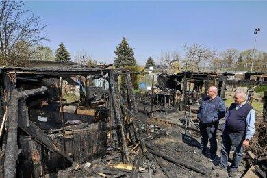 """Winfried Hauschild (rechts) und Matthias Zimmermann vom Vorstand des Kleingartenvereins sehen sich den Schaden an, den ein Brand in der Anlage """"Gartenfreunde"""" angerichtet hat."""