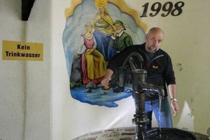 """Fünf Jahrhunderte lang galt der """"Gute Brunnen"""" zwischen Zwönitz und Affalter als Heilquelle. Wasser führt sie immer noch, wie Willi Kreutel mit seinem Pumpen beweist, aber trinken kann man es nicht mehr."""