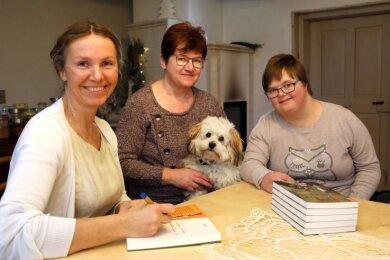 Wilma Staffa (links) signiert ihr Buch. Es ist für Christin Metzner und deren Tochter Theresa, die mit Hund Hansi zu Besuch sind.