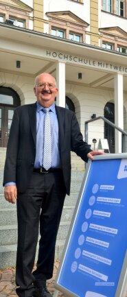 Rektor Professor Ludwig Hilmer übt sich in der Willkommenspose vor dem Haupthaus der Hochschule Mittweida, verweist aber zugleich auf die strengen Hygieneregeln für das neue Semester.