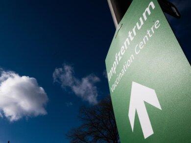 Ein Schild mit einem Pfeil weist den Weg zu einem Impfzentrum.