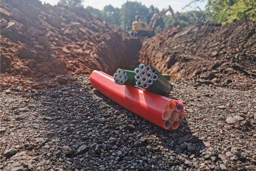 In die Rohre im Vordergrund werden später die Glasfaserleitungen geblasen. Im Hintergrund ein Bagger bei Schachtarbeiten. .