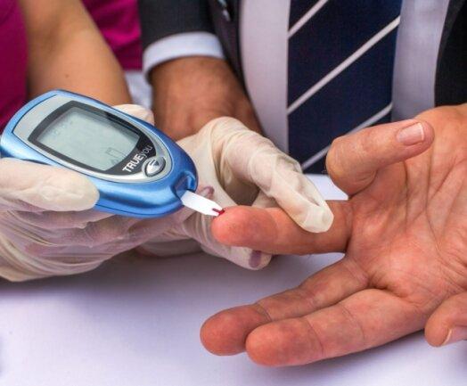 Ein Mann lässt sich von einer Diabetesberaterin eine Blutprobe für einen Blutzuckertest nehmen. Die Zahl der an Diabetes Typ 2 erkrankten Menschen in Deutschland wird nach neuen Berechnungen viel stärker ansteigen als bisher prognostiziert.