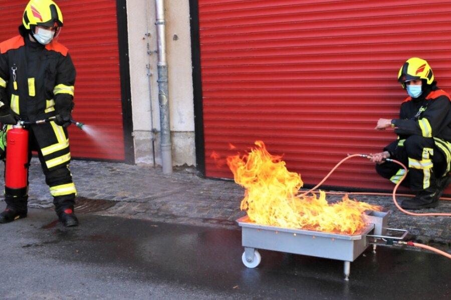 Lucas Baumann (l.) und der stellvertretende Leiter der Ortsfeuerwehr Eppendorf, Robby Kluge, testen die Feuerlöscherübungsanlage.