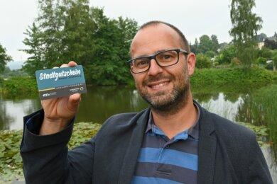 Innenstadtmanager Stefan Herold mit einem Stollberger Stadtgutschein im Scheckkartenformat.