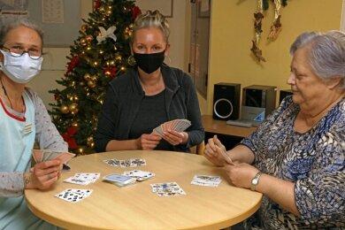 Willkommene Ablenkung in Zeiten der Pandemie: Die Alltagsbegleiterinnen Irena Thierfelder und Sandra Maercz (von links) spielen im Werdauer DRK-Pflegeheim mit Bewohnerin Renate Graupner Kartenspiel.