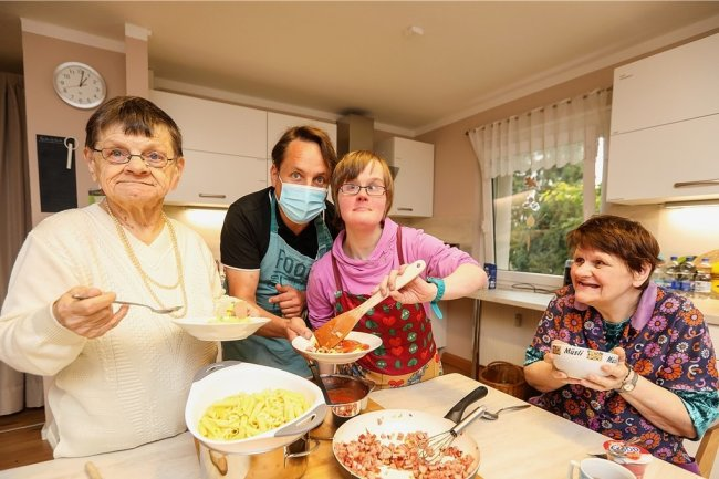 Nach dem gemeinsamen Kochen kommt das Essen in geselliger Runde. Hier machten sich in der Küche Ingrid, Projektverantwortlicher Steve Hübner, Nancy und Veronica (von links) nützlich.