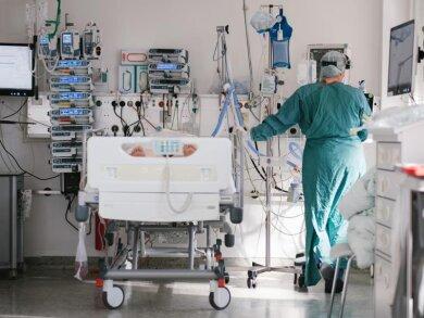 Eine Pflegerin versorgt auf der Intensivstation am Klinikum Braunschweig einen an Covid-19 erkrankten Patienten. Laut DIVI ist die Lage auf den Intensivstationen bundesweit immer noch sehr angespannt.