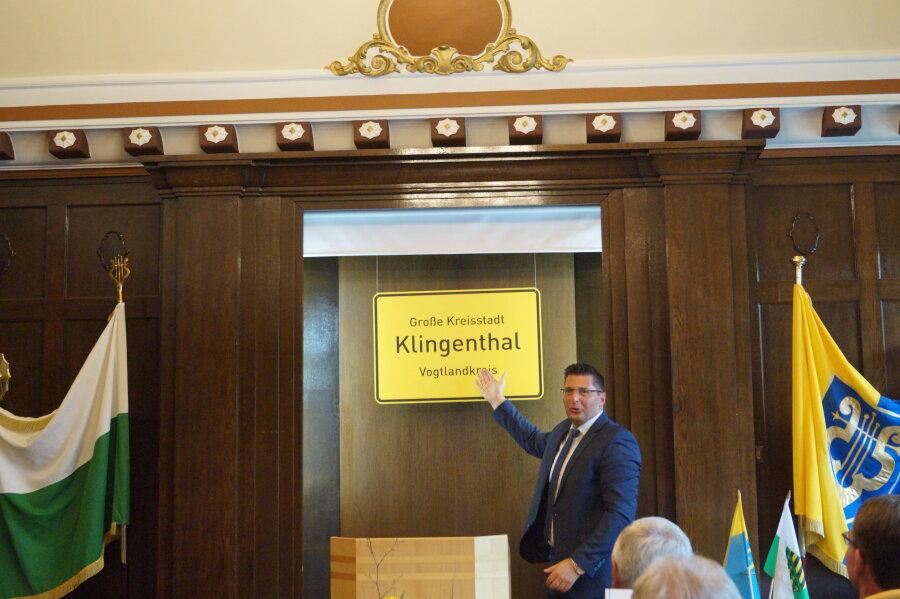 Bürgermeister Thomas Hennig zeigt stolz das neue Ortsschild von Klingenthal.
