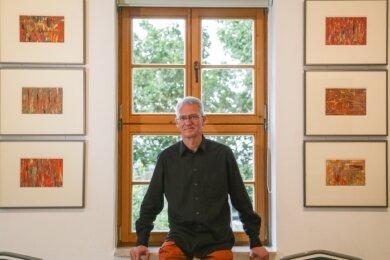 """Karsten Mittag in der Ausstellung seiner Bilder (im Foto die, die zum Musiksommer 2019 entstanden sind) im """"Lotterhof"""" in Augustusburg."""
