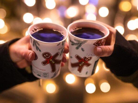 Zwei Besucherinnen eines Weihnachtsmarktes stoßen mit Glühwein an.