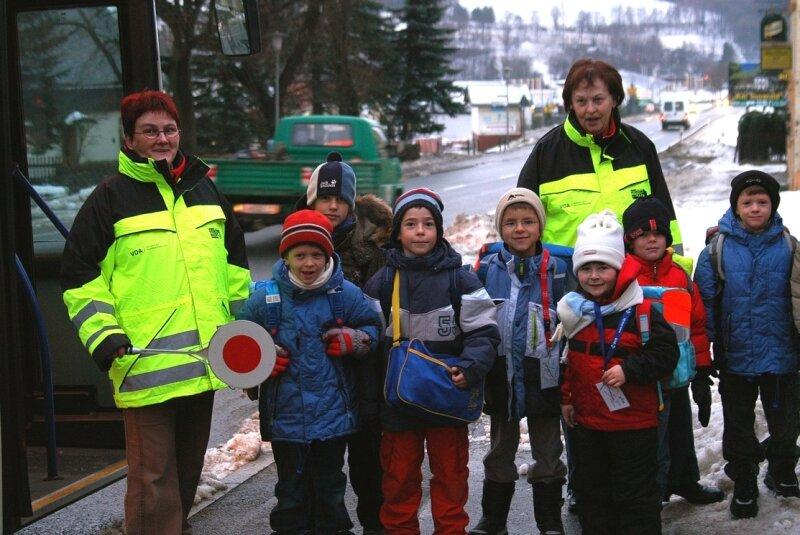 Jutta Bochmann (l.) und Petra Walther sind Schulweghelferinnen in Schönfeld. Die Kinder Richard, Willy, Robin, Tim, Sophia, Cornelius und Georg (v. l.) fühlen sich bei ihnen sicher.