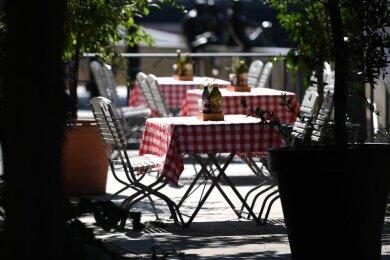 Leere Tische stehen vor einem Restaurant in Berlin. Die Corona-Krise sorgt weiter für Einbußen in der Gastronomie.