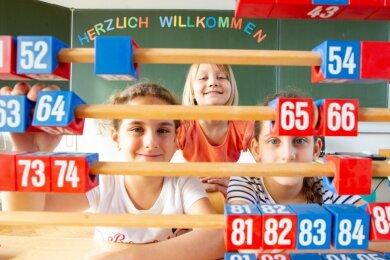 """Alles ist bereit für den Schulanfang am Montag. ...Farah, Emily und Lamar (von links) warten schon auf die Abc-Schützen. An die Tafel haben sie einen Gruß geschrieben: """"Herzlich willkommen""""."""