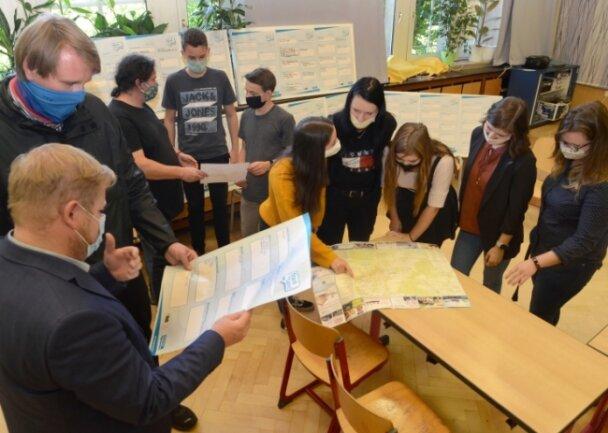 Bürgermeister Marco Siegemund (CDU), die Projektbetreuer von der Deutschen Kinder- und Jugendstiftung, der Schülerrat und die beteiligten Lehrerinnen (von links) begutachteten in der Aula der Trützschler-Oberschule die Vorschläge der Schüler.