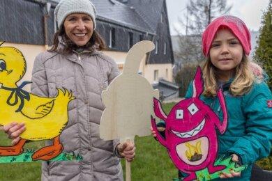 Sandra Beyer und ihre Tochter Julie auf dem Gelände des Familienzentrums, für dessen Spielplatz die Aktion gedacht ist. Sie zeigen zwei bemalte Figuren sowie einen Rohling, der noch auf einen Käufer wartet.