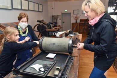 Helena Kästner aus Kleinschirma (l.) besuchte mit Mutter Jaqueline (r.) das Webmuseum Oederan. Hier wird historische Technik des Druckens hergestellt, die von Christine Schulze erklärt wird. Die dicke Rolle, mit der das Papier angedrückt wird, heißt Nudel.