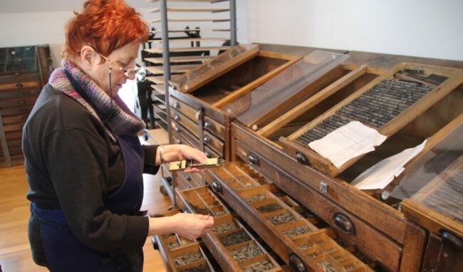 Christine Schulze fügt in der Druckwerkstatt Oederan in einem Winkelhaken alle Lettern in Spiegelschrift aneinander.