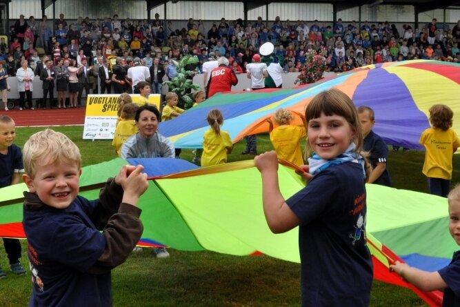 Ein Bild aus einer anderen Zeit. Es zeigt junge Sportlerinnen und Sportler sowie eng beieinander stehende Gäste bei der Eröffnung der Vogtlandspiele vor sieben Jahren im Stadion Falkenstein.