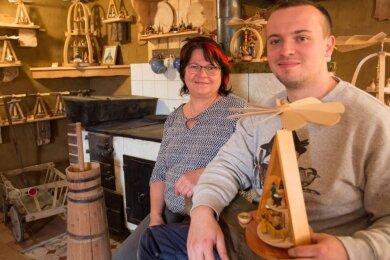 Annett und Christian Neuber sitzen auf der Ofenbank im historischen Musterzimmer des Familienunternehmens.