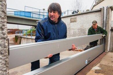 Flussmeister Toralf Weiß (links) und Vorarbeiter Jörn Müller von der Flussmeisterei Neidhardtsthal testen das mobile Wehr, das in der Nähe der Wasserstraße gebaut wurde.