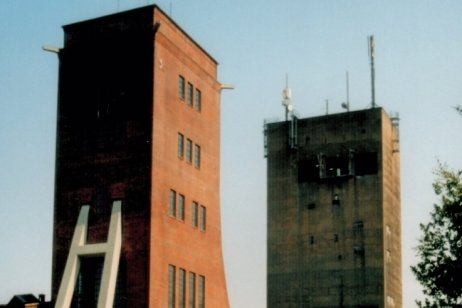 Das Foto zeigt die Fördertürme der Martin-Hoop-Schächte IV und IVa von Süden. Der vordere Turm (Schacht IV) ist 40 Meter, der hintere Schacht IVa 60 Meter hoch. Mittlerweile bringen zwei riesige Graffiti etwas Schwung auf die Fassade von IVa.