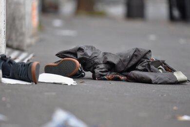 """Schuhe und Kleidungsstücke liegen am 14. November 2015 in Paris vor dem Musikclub """"Bataclan"""" auf dem Boden.Extremisten hatten am Tag zuvor in diesem Konzerthaus ein Massaker angerichtet und dort 90 Menschen erschossen. Außerdem beschossen sie Bars und Restaurants im Osten der französischen Hauptstadt. Insgesamt töteten die Attentäter in Paris 130 Menschen."""