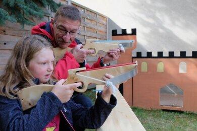 Michael Thümmler vom Kultur- und Freizeitzentrum Lugau zeigt der achtjährigen Lilly beim Ritterfest, wie sie beim Armbrustschießen richtig anlegen muss.