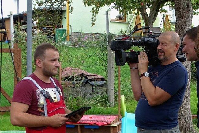"""Frederic Schaarschmidt (links) steht dem Team des MDR für die Sendung """"Unser Dorf hat Wochenende"""" in Reumtengrün Rede und Antwort. Foto: Andreas Leidel"""