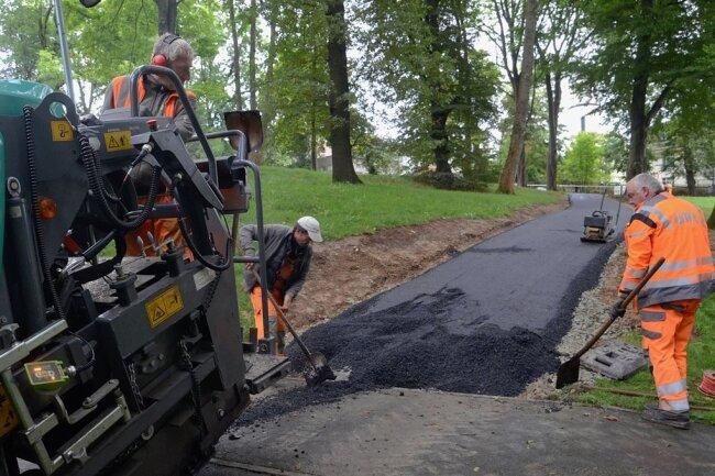 Am Freitag baute ein Team der Firma UTR die Schwarzdecke in den neuen Weg im Stadtpark ein. Am Montag soll die Strecke für Fußgänger, Radler und Rollstuhlfahrer freigegeben werden.