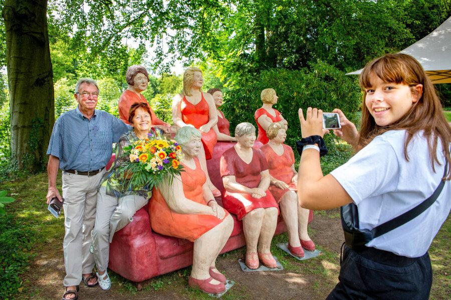 """Heidrun und Wolfgang Bloi nehmen auf dem roten Sofa der Ausstellung """"Alltagsmenschen"""" von Christel Lechner Platz, Enkelin Fiona Michel hält es fotografisch fest."""