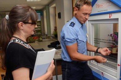 In Sekunden stemmt Polizist Markus Meichsner ein Fenster per Schraubendreher auf. Kerstin Galko ist beeindruckt.