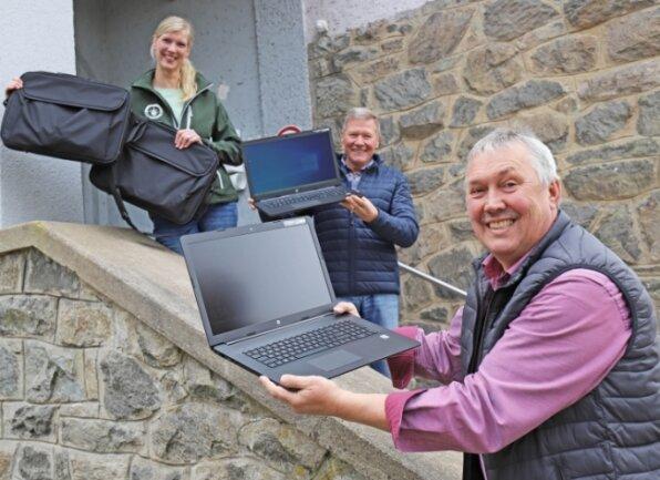 Julia Pergande nimmt die Laptops samt Taschen von den Lions Frank Pillau und Volker Haupt (v.l.) entgegen.