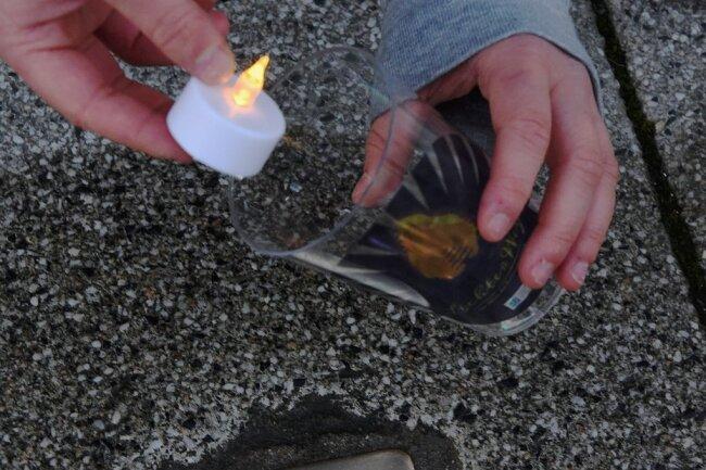 Ingo Kübeck von den Buntmacherinnen platziert ein Licht vor einem Stolperstein am ehemaligen Kaufhaus Schocken.