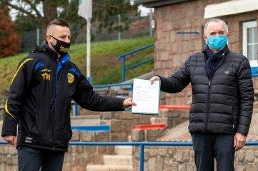 Thommy Haeder erhält von Regionalminister Thomas Schmidt einen Fördermittelscheck für den Neubau einer Sporthalle.