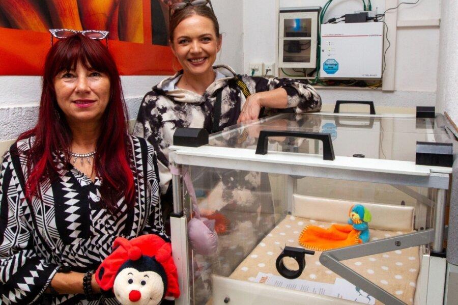 Karo-Vereinschefin Cathrin Schauer-Kelpin und Mitarbeiterin Eileen Schönheit (von links) hinter der Plauener Babyklappe. Vor gut einem Jahr wurde der bislang letzte Säugling dort abgelegt.